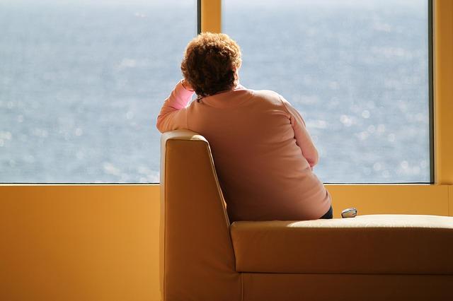 Femme installée sur un canapé face à une vue sur la mer dans un cabinet de thérapie EMDR.