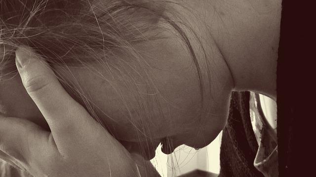 Femme qui pleure la tête dans les mains.