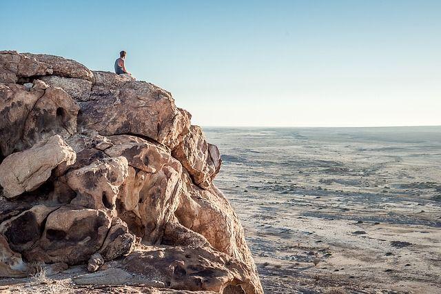 C'est un paysage avec un homme assis de dos.