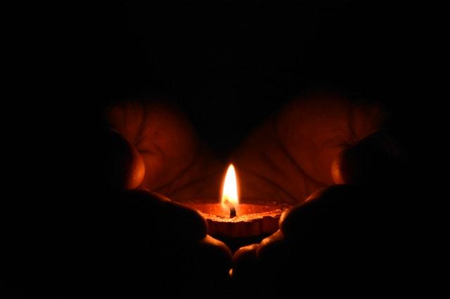 Flamme de bougie entre des mains.
