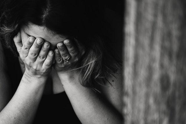 Jeune femme triste qui se prends la tête entre les mains