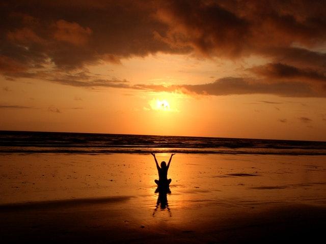 Personne en pleine méditation sur la plage.